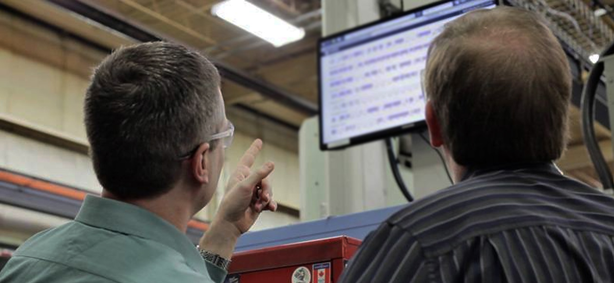 men looking and pointing at monitor with Shiftworx data displayed in factory freepoint technologies