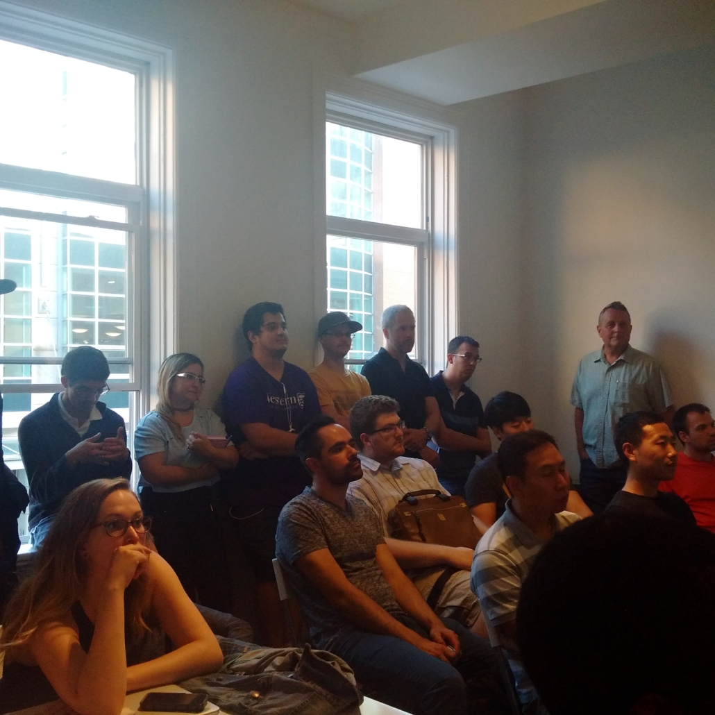 people sitting and standing in front of windows watching speaker freepoint technologies