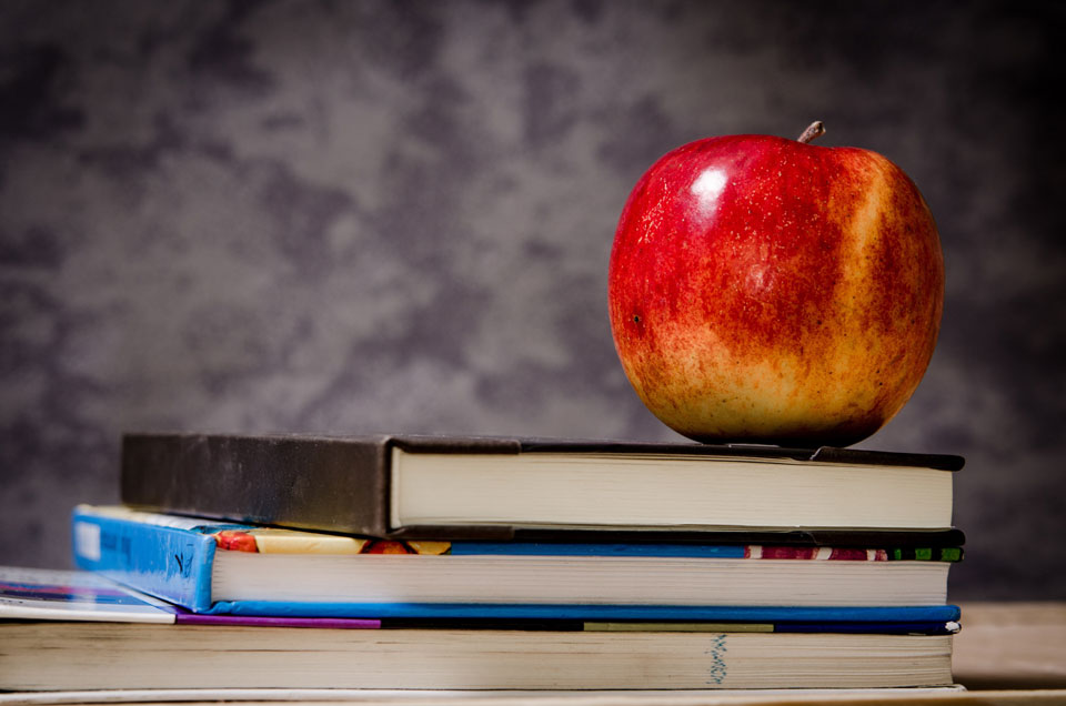 apple sitting on text books on wooden table purple and white smoky background freepoint technologies