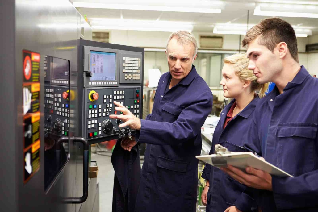 engineer teaching apprentices to use computerized lathe student with clipboard in factory freepoint technologies