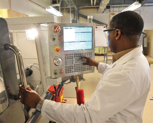 man in factory lab coat operating machine control panel stainless steel door