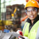 factory man orange helmet reflective vest clipboard gloves writing freepoint technologies