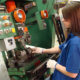 woman working machine in factory transformer cores green machine buttons lights gloves freepoint technologies