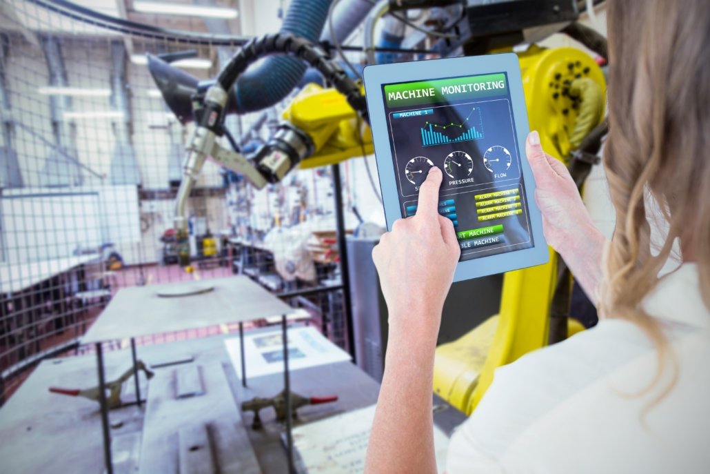 Woman using tablet for machine monitoring in factory robotic arm in background freepoint technologies