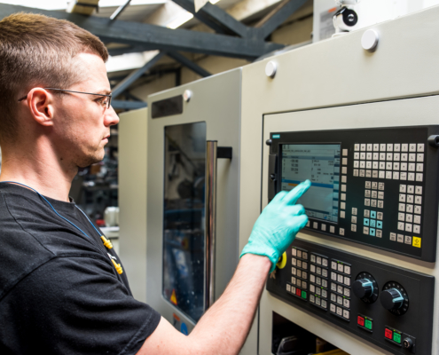 man programming a CNC machine on factory floor wearing surgical gloves freepoint technologies