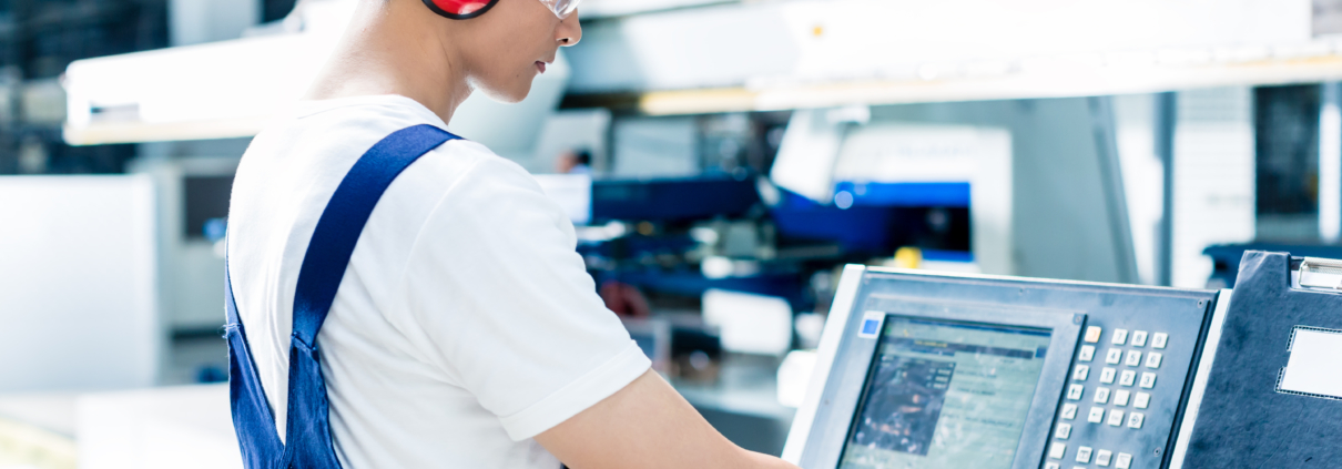 Machinist enderting data into CNC machine on factory floor freepoint technologies