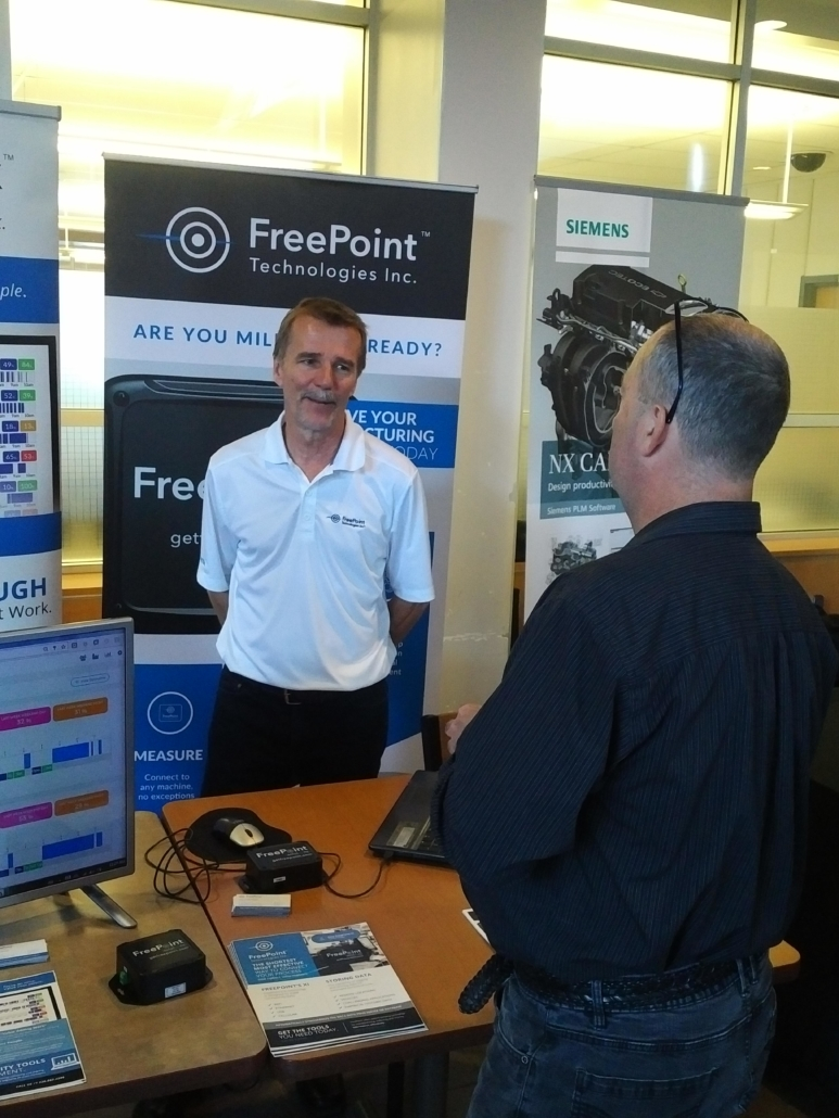 freepoint technologies president stand with man in front of shiftworx and freepoint and siemens posters shiftworx software visible on monitor in foreground