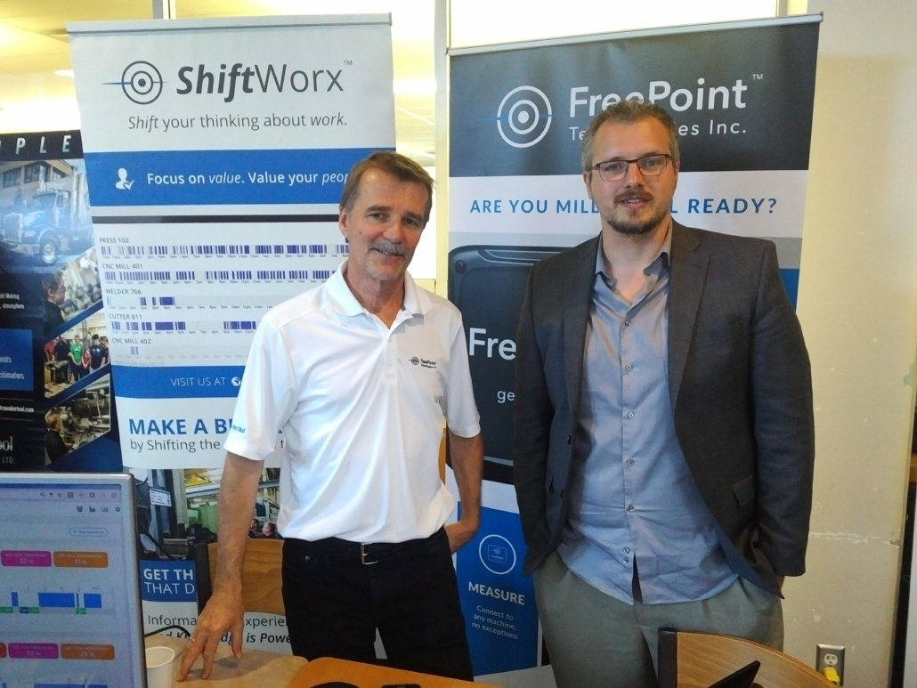 freepoint technologies president stand with man in front of shiftworx and freepoint posters shiftworx software visible on monitor in foreground
