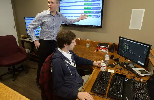 man pointing at monitor displaying shiftworx software developer writing code at computer freepoint technologies
