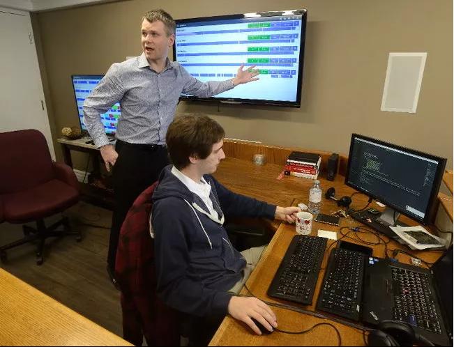 man pointing at monitor displaying shiftworx software developer writing code at computer freepoint technologies