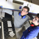two factory workers with safety glasses looking at monitor one pointing at something on the screen freepoint technologies