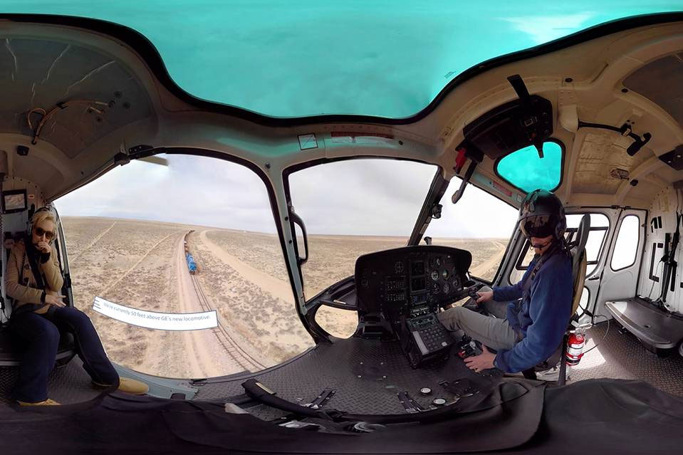 panorama of inside of helicopter hovering above train tracks with oncoming train freepoint technologies