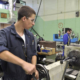 Man working lathe in factory center drill metal piece freepoint technologies