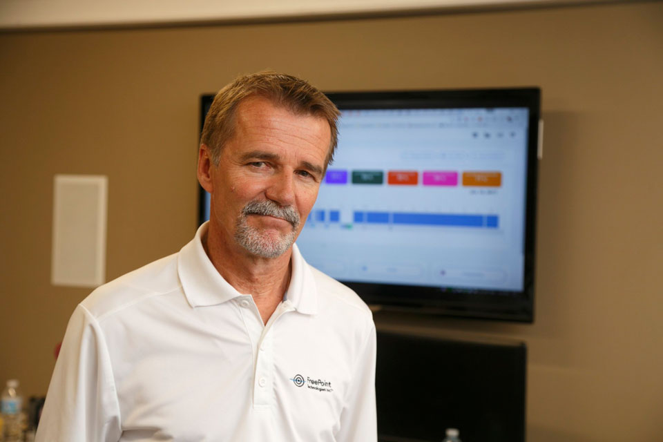 freepoint technologies president standing in front of monitor displaying shiftworx software
